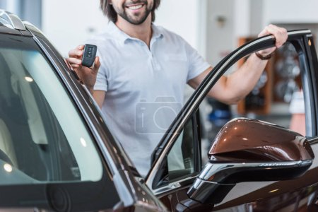 cropped shot of smiling man with car key standing at new car in dealership salon