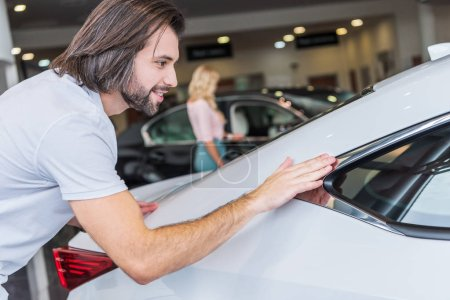 selective focus of man checking automobile with girlfriend on background at dealership salon