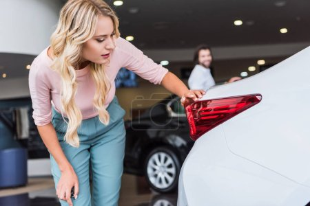 selective focus of woman checking automobile with boyfriend on background at dealership salon