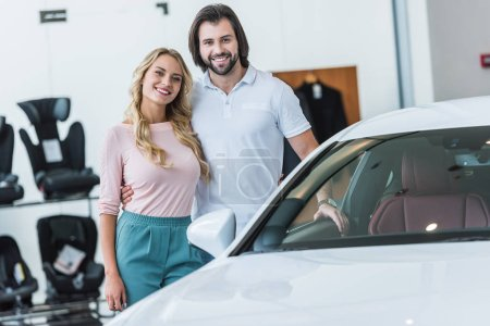 portrait of happy couple hugging at new car at dealership salon