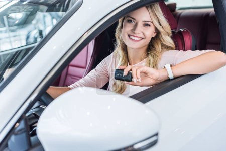 portrait of smiling woman with car key in hand sitting in new car in dealership salon
