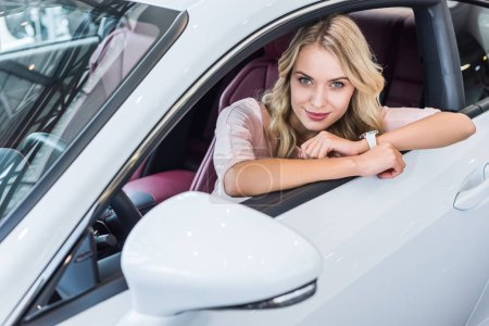 portrait of young woman looking at camera while sitting in new car in dealership salon