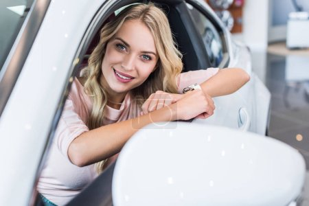 portrait of smiling woman sitting in new car in dealership salon