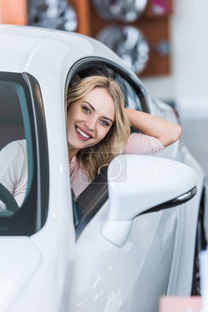 portrait of happy young woman sitting in new car in dealership salon