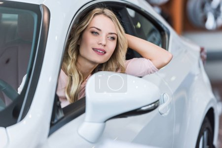 portrait of young woman sitting in new car in dealership salon