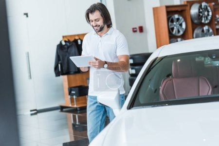 smiling man using digital tablet in hands at dealership salon