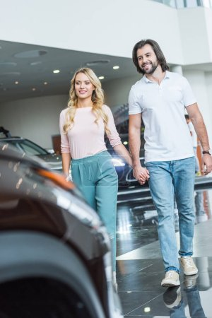 happy couple holding hands while walking at dealership salon