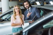 seller in formal wear recommending automobile to woman at dealership salon