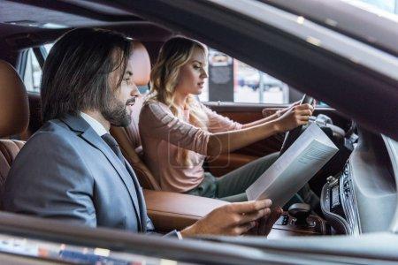 Photo pour Concessionnaire vendeur de salon et client féminin assis en voiture dans le salon de l'automobile - image libre de droit