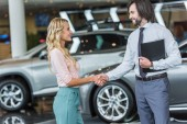 side view of dealership salon shop assistant and female customer shaking hands in auto salon