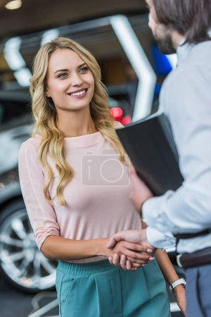 partial view of dealership salon shop assistant and smiling female customer shaking hands in auto salon