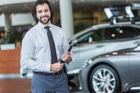 smiling seller with folder standing in dealership salon with cars on background