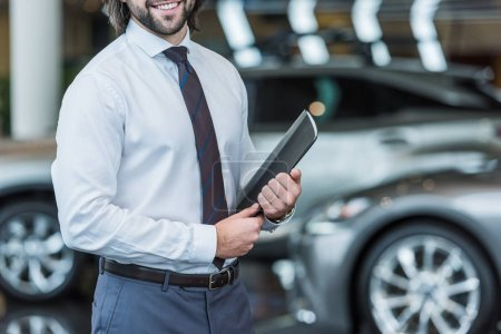 Photo for Cropped shot of seller with folder standing in dealership salon with cars on background - Royalty Free Image