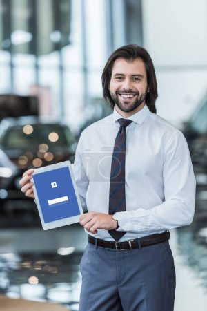 smiling dealership salon seller in formal wear showing tablet with facebook logo on screen in hands