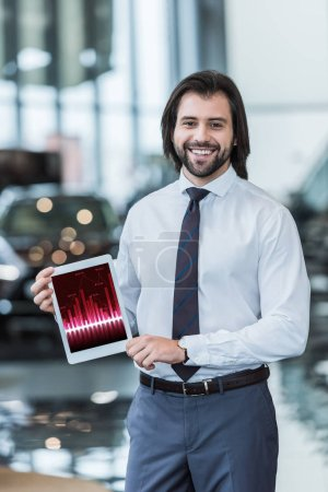smiling dealership salon seller in formal wear showing tablet with infographic in hands