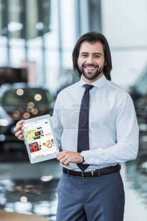 smiling dealership salon seller in formal wear showing tablet with ebay website on screen in hands