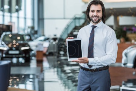 portrait of smiling seller in formal wear showing tablet with blank screen at dealership salon