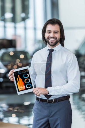 smiling dealership salon seller in formal wear showing tablet with graphic diagram in hands