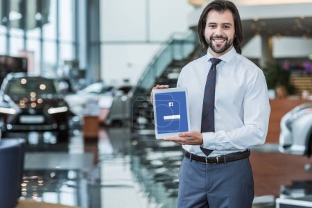 portrait of cheerful dealership salon seller in formal wear showing tablet with facebook logo on screen in hands
