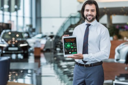 portrait of cheerful dealership salon seller in formal wear showing tablet with marketing analysis in hands