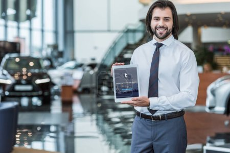 portrait of cheerful dealership salon seller in formal wear showing tablet with twitter logo on screen in hands