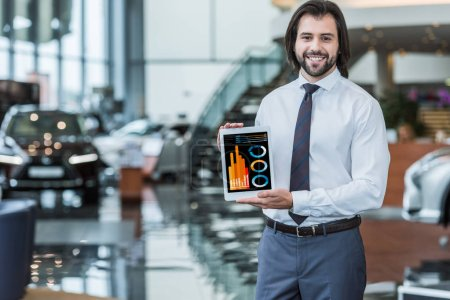 portrait of cheerful dealership salon seller in formal wear showing tablet with infographic in hands