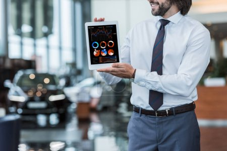 partial view of dealership salon seller in formal wear showing tablet with infographic in hands