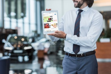 partial view of dealership salon seller in formal wear showing tablet with ebay website in hands