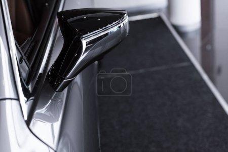close up view of grey luxury car at dealership salon