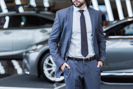 partial view of businessman in stylish suit standing in dealership salon with new cars on background