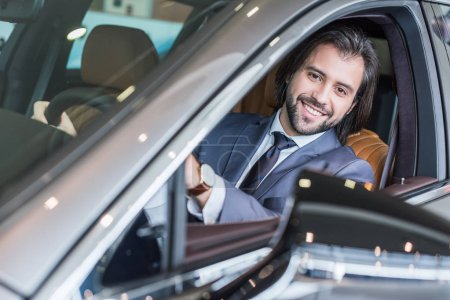 portrait of businessman sitting in new car for test drive in dealership salon