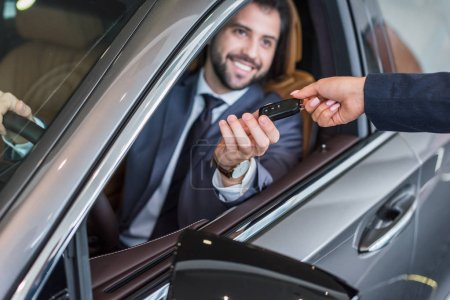 partial view of female seller giving car key to smiling businessman in new car at dealership salon