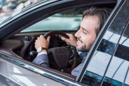 smiling businessman sitting in new car for test drive in dealership salon