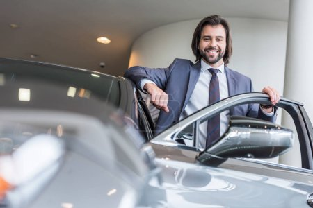 happy stylish businessman standing at new car at dealership salon
