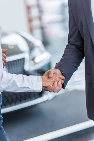 cropped shot of auto salon seller and businessman shaking hands at dealership salon