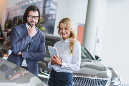 Photo for Smiling female auto salon seller with tablet helping businessman to choose car at dealership salon - Royalty Free Image