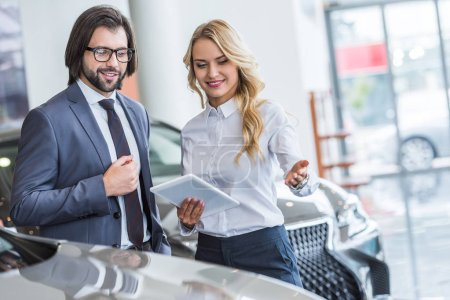 female auto salon seller with tablet helping businessman to choose car at dealership salon