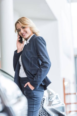 smiling businesswoman in stylish suit talking on smartphone in dealership salon