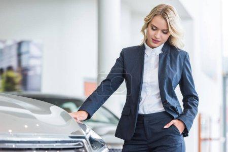 portrait of stylish businesswoman in suit choosing car in dealership salon