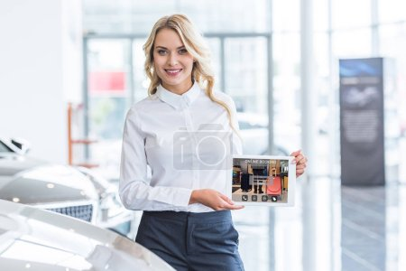 portrait of smiling seller showing tablet with online booking website on screen in hands in dealership salon