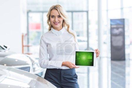 Photo pour Portrait du vendeur souriant montrant la tablette avec le diagramme graphique dans les mains dans le salon de concession - image libre de droit