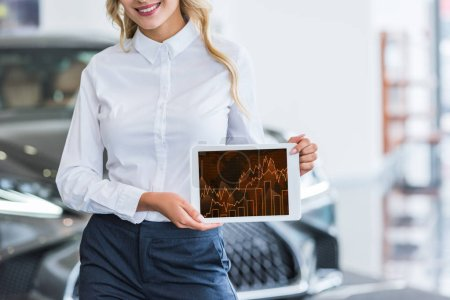 partial view of female seller showing tablet with graphic diagram in hands in dealership salon