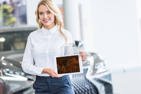 portrait of smiling seller showing tablet with graphic diagram in hands in dealership salon