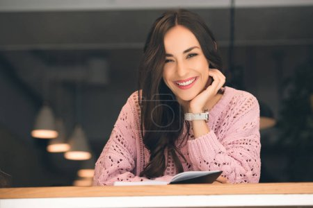 happy young woman sitting with book at table in cafe