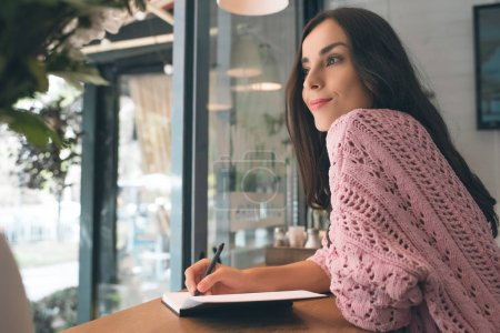 Photo pour Souriant jeune femme prenant des notes dans le manuel à la table dans le café - image libre de droit