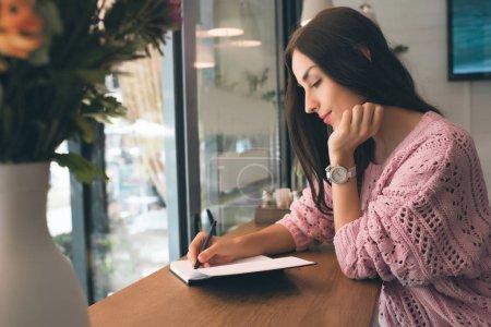 Photo pour Vue latérale de la jeune femme, prendre des notes en manuel à table à café - image libre de droit