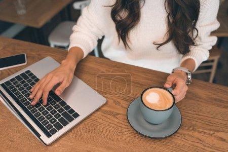 Photo pour Vue partielle des femelle pigiste travaillant sur ordinateur portable assis à table avec smartphone et café tasse à café - image libre de droit