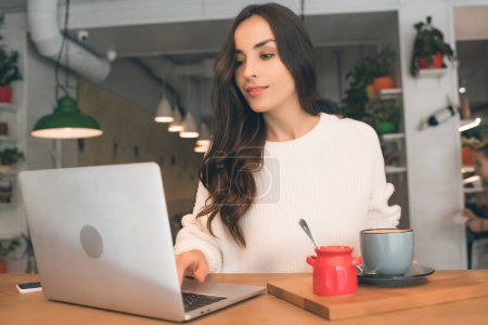 Photo for Young female freelancer working with laptop and coffee cup at table in cafe - Royalty Free Image