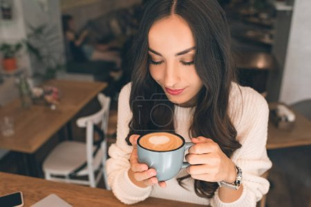 high angle view of young attractive woman drinking coffee at table in cafe