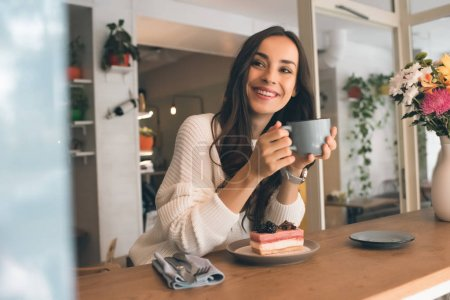 Photo for Happy young woman with coffee cup sitting at table with cheesecake in cafe - Royalty Free Image